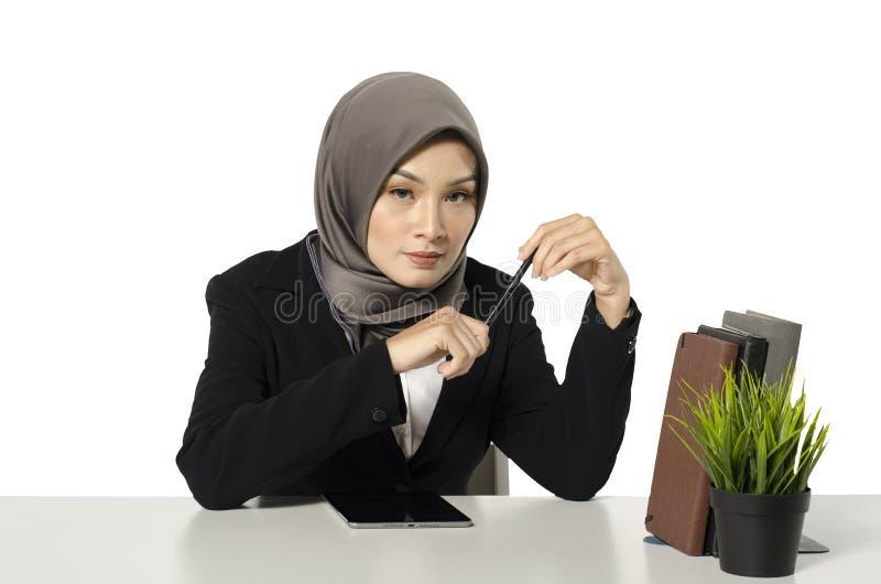 Ufny wyrażeniowy młody uśmiechający się fachowy bizneswoman siedzi nad białym tłem fotografia stock