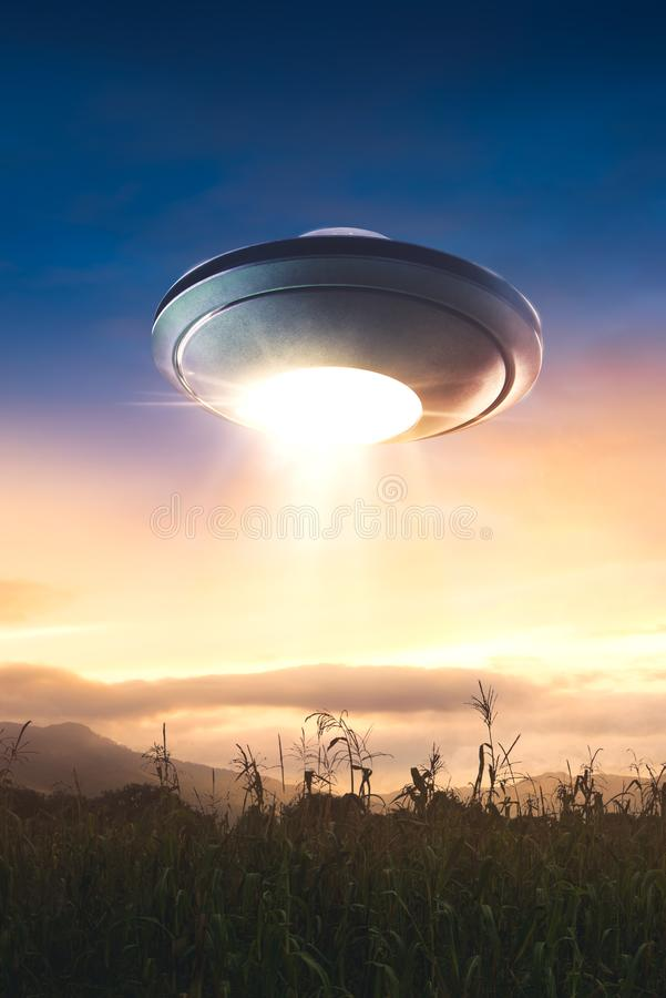 UFO with abduction beam flying in the sky stock photo