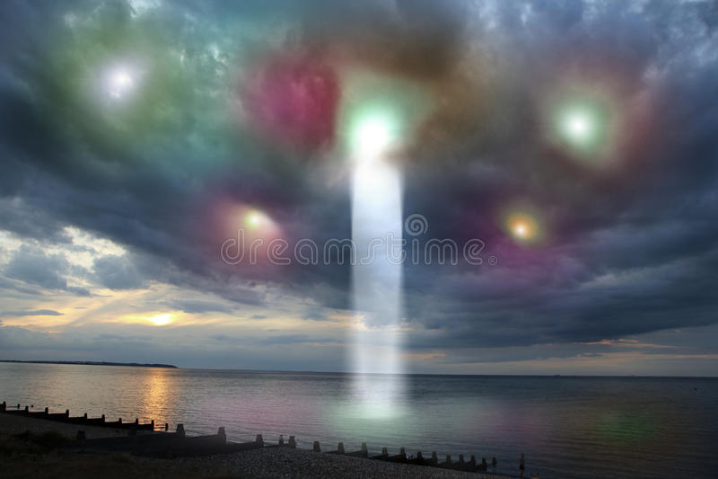 Ufo arrival. Concept photo of a coastal storm cloud hiding the arrival of a ufo which has sent down an energy light beam royalty free stock photos