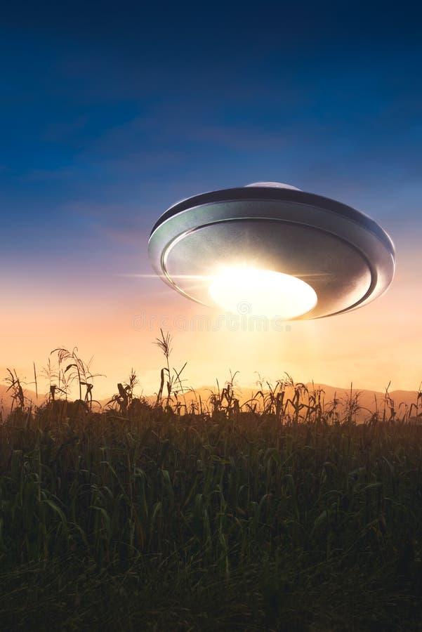 UFO con el vuelo del haz de la abducción en el cielo foto de archivo libre de regalías