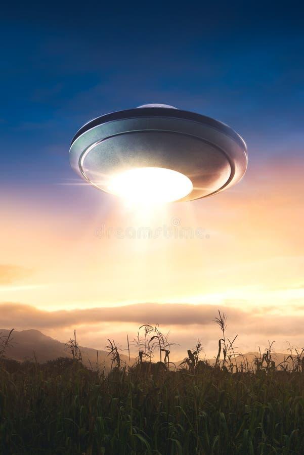 UFO con el vuelo del haz de la abducción en el cielo foto de archivo