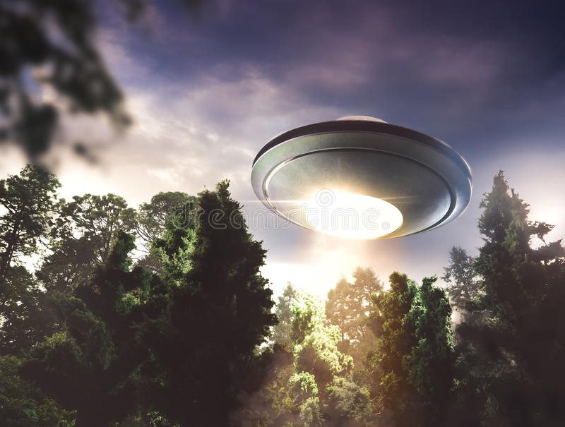 UFO flying over a forest. UFO hovering over a forest at dusk royalty free stock image