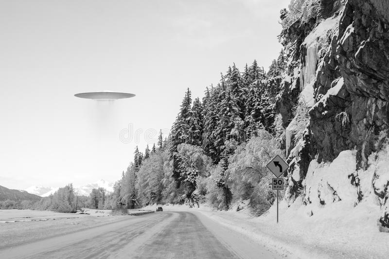 UFO over Alaskan road. UFO space ship hovering over an Alaskan road in winter with a car in the distance stock photo