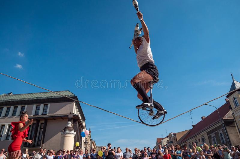 Clown and acrobat riding bicykle on rope during UFO street festival - international meeting of street performers and actors stock photography