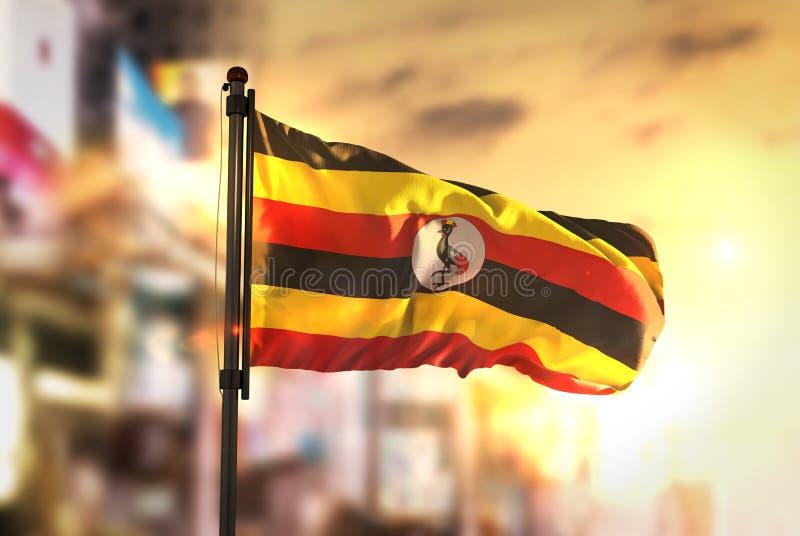 Uganda Flag Against City Blurred Background At Sunrise Backlight. Sky stock photos