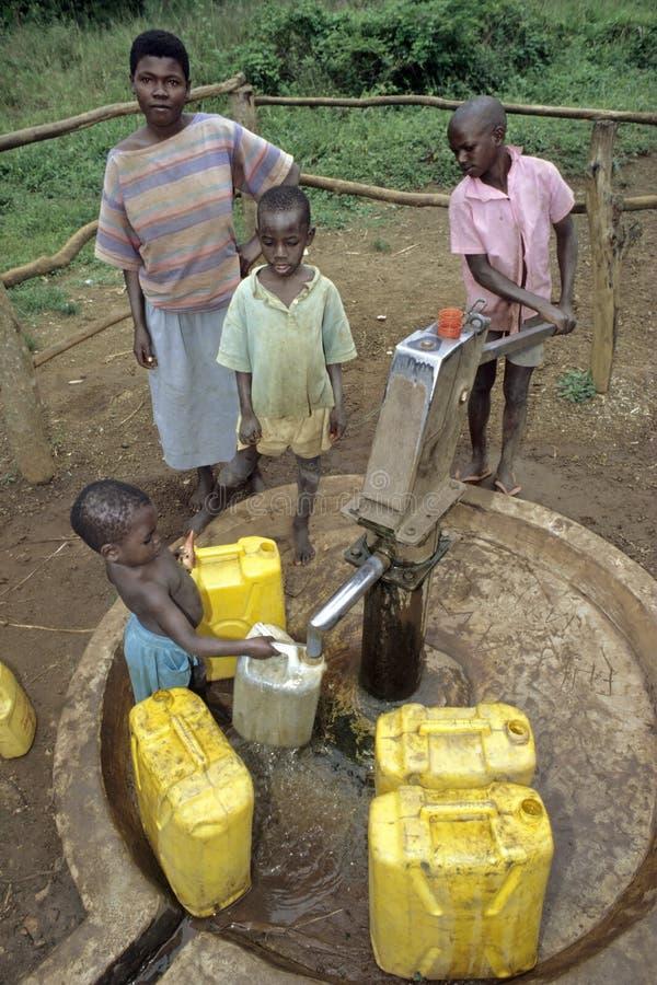 Ugandan Kinderen halen water bij waterpomp stock afbeeldingen