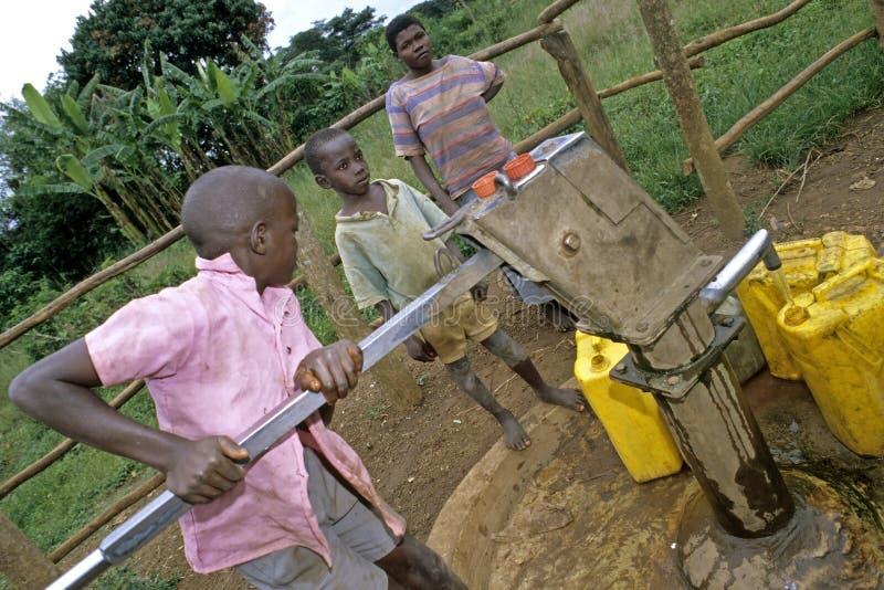 Ugandiskt barnfetchvatten på vattenpumpen royaltyfri bild