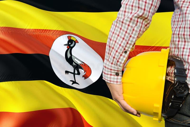 Ugandyjski inżynier trzyma żółtego zbawczego hełm z machać Uganda chorągwianego tło Budowy i budynku poj?cie obrazy stock