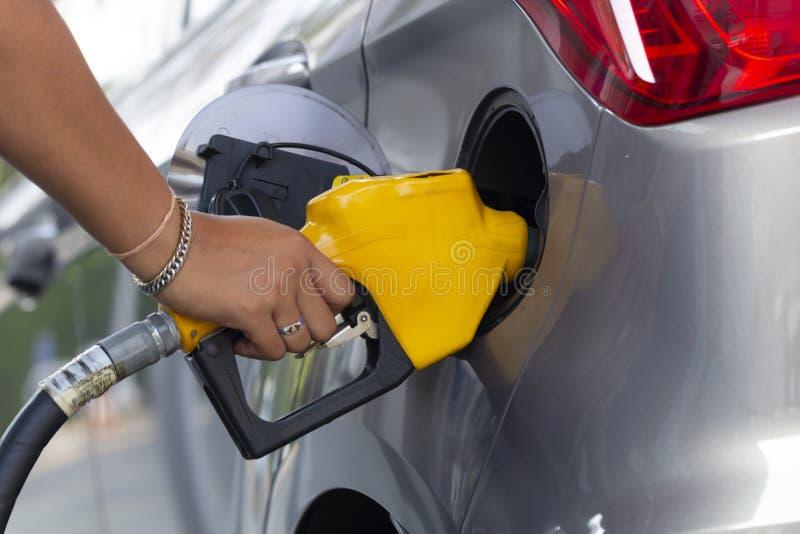 Ugelli di riempimento della pompa di benzina dell'olio nel servizio della stazione di servizio fotografia stock