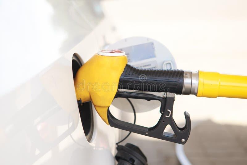 Ugelli di riempimento della pompa di benzina variopinta isolati su fondo bianco, stazione di servizio in un servizio nel tramonto immagini stock