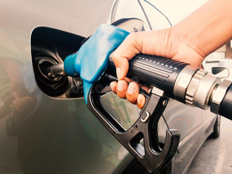 Ugello della benzina della tenuta della mano alla stazione di servizio fotografie stock libere da diritti