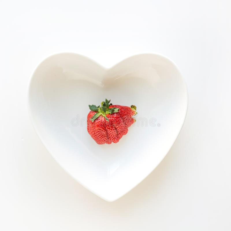 Ugly one ripe organic strawberry in plate as heart isolated on white background. View from above royalty free stock photos