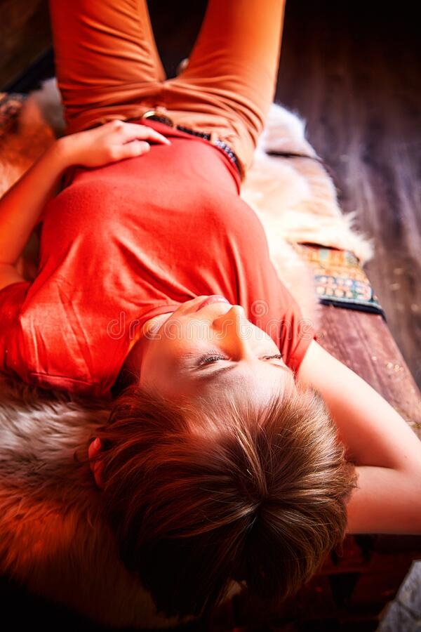 Ugly pity girl in red dress on the couch with hay in the room or in the hayloft with wooden walls. Rustic style in the interior. During photoshoot stock images