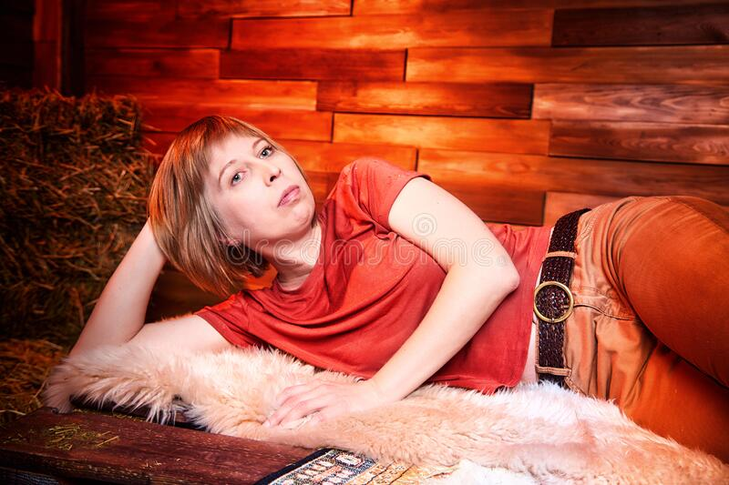 Ugly pity girl in red dress on the couch with hay in the room or in the hayloft with wooden walls. Rustic style in the interior. During photoshoot stock photos