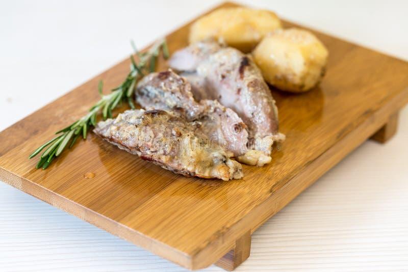 Ugn lagat mat lamm med potatisar ombord arkivbilder
