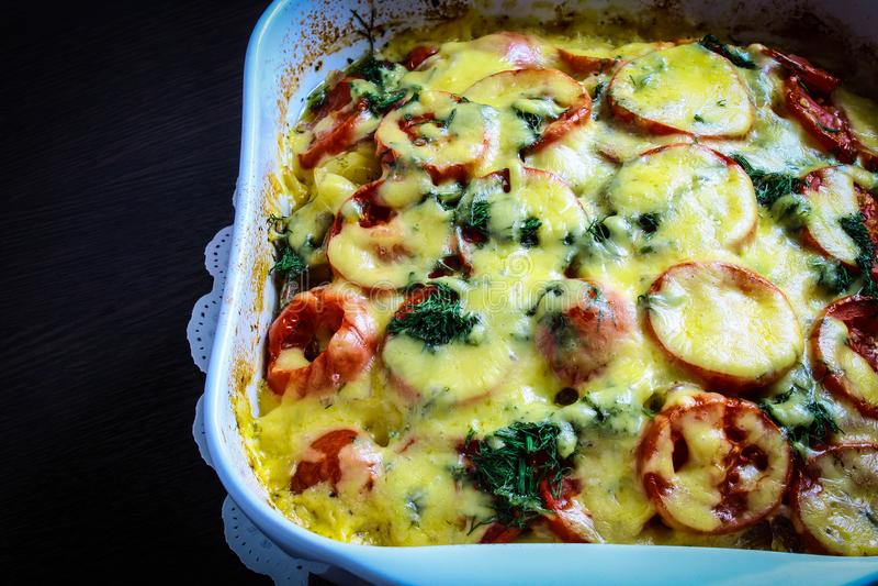 Ugnseldfast form - potatisar med kött, tomater, ost, örter, lökar och kryddor royaltyfria bilder