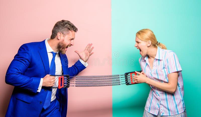 Uguaglianza di genere e distinzione Concetto di rivalità di genere Uomo e donna che allungano i lati opposti dell'estensore Affar fotografia stock