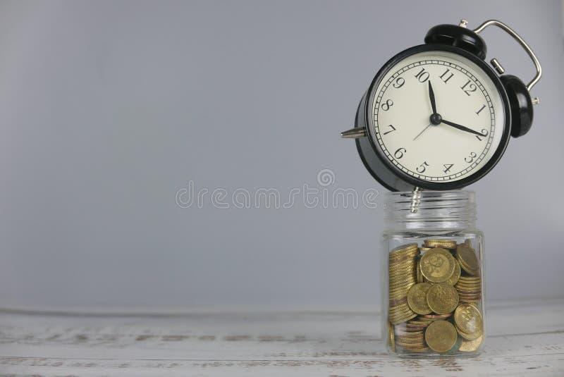 Uhr über Glas Goldmünzen Geld und Zeitkonzept Kopieren Sie Raum f?r Text oder Logo lizenzfreies stockbild