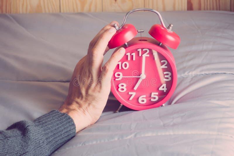 Uhr auf dem Bett am Morgen stockbild