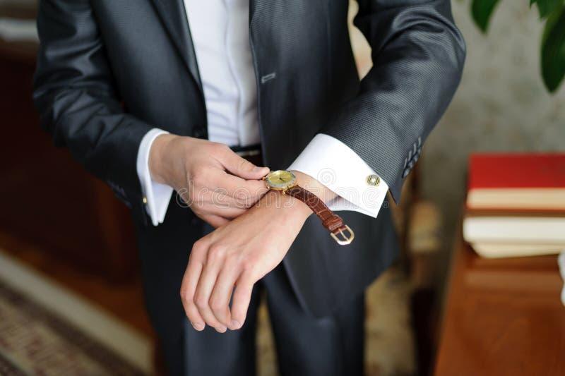 Uhr auf der Hand des Bräutigams stockfotografie