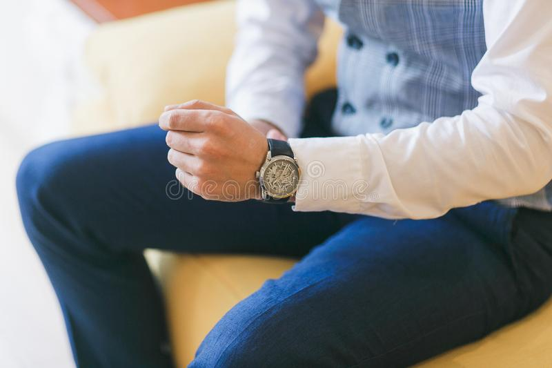 Uhr auf Mann ` s Hand Bräutigam, der für Hochzeitszeremonie sich vorbereitet Selektiver Fokus lizenzfreie stockfotos