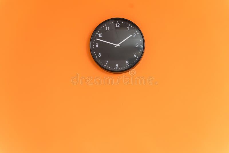 Uhr auf orange Wand stockfotografie