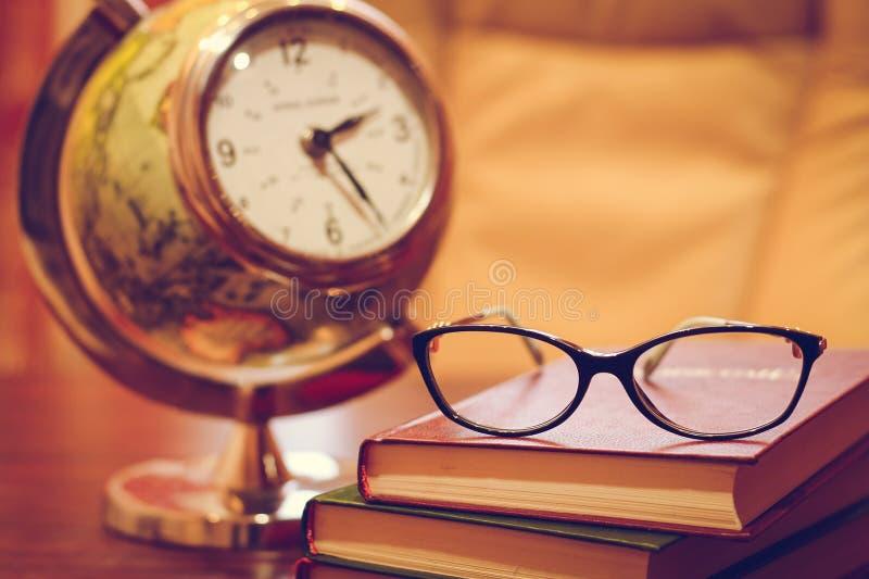 Uhr, Gläser und Bücher auf dem Tisch stockfotos