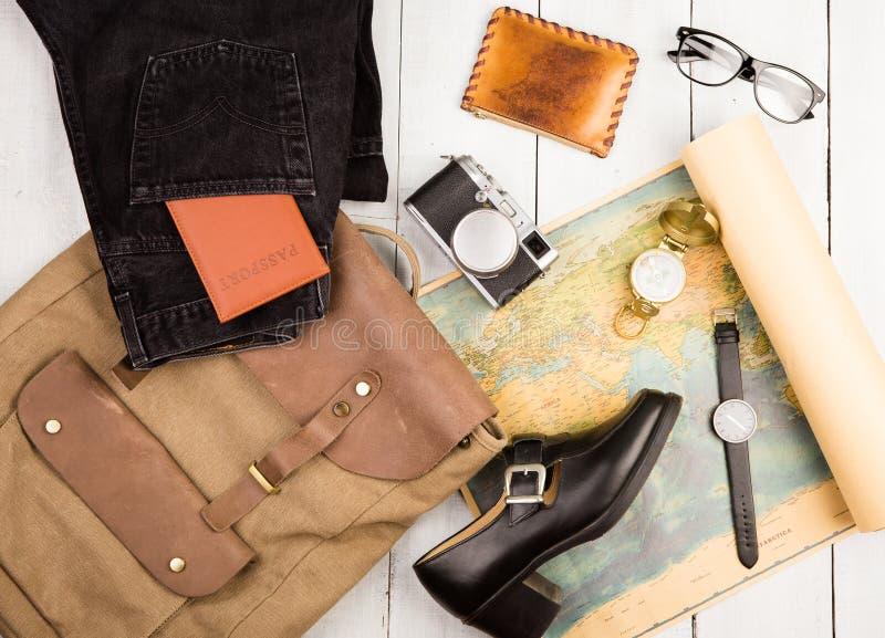 Uhr, Kamera, Gläser, Rucksack, Schuh, geographische Karte, Pass, Kompass, Geldbeutel auf weißem Holztisch stockbild