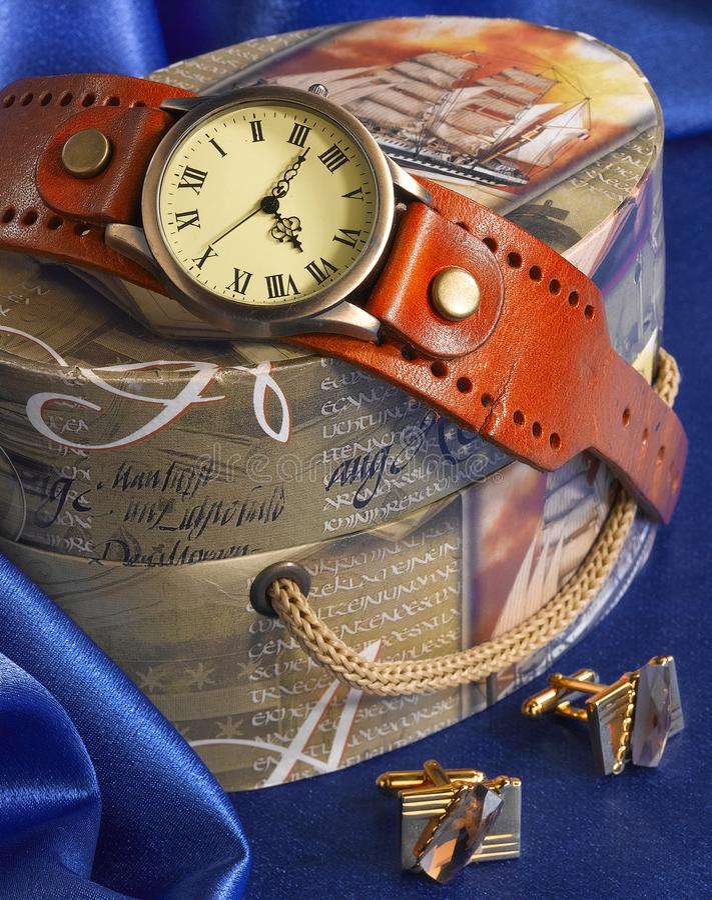Uhr, Manschettenknöpfe und Geschenkbox auf blauem Hintergrund stockfotos