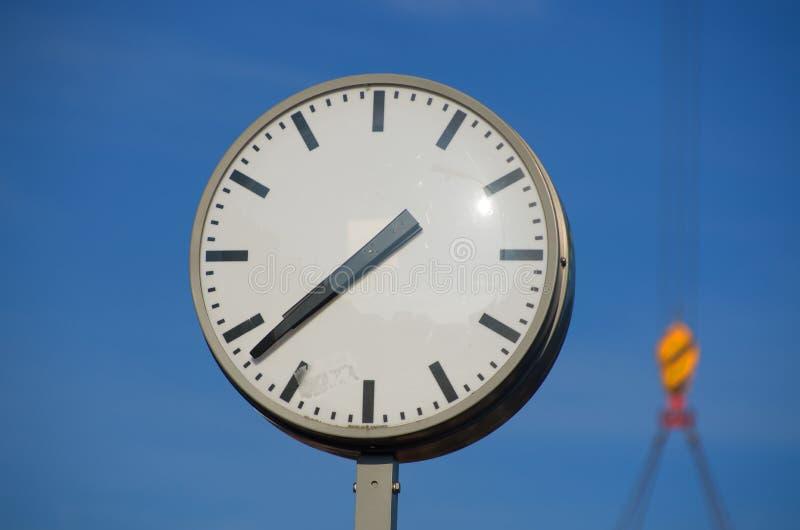 Uhr mit Hebemaschine im Hintergrund stockfoto