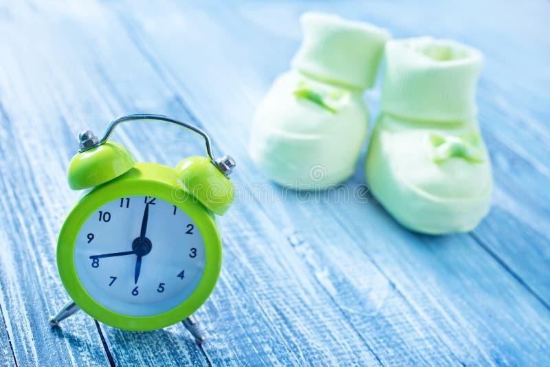 Uhr- und Babysocken stockfotos