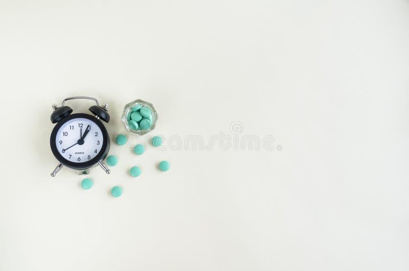 Uhr und Pillen kommen von einer Medizinflasche heraus Pillenzeit Kopieren Sie Platz stockbild