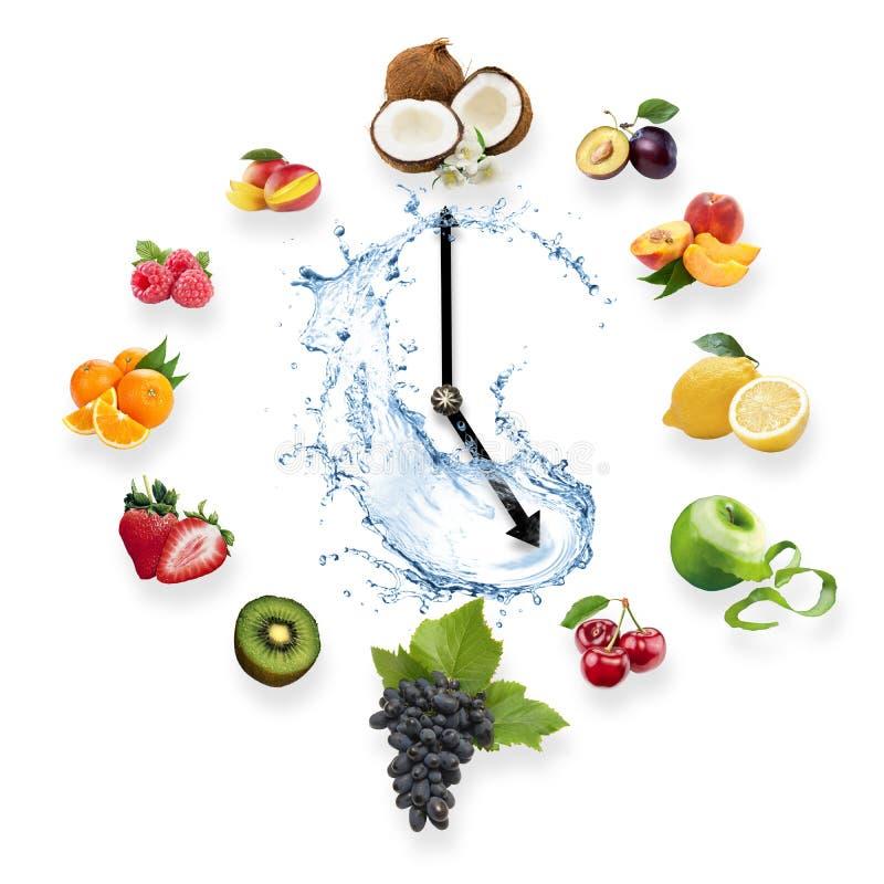 Uhr vereinbarte von den gesunden Früchten spritzen durch das Wasser, das auf w lokalisiert wurde lizenzfreies stockbild