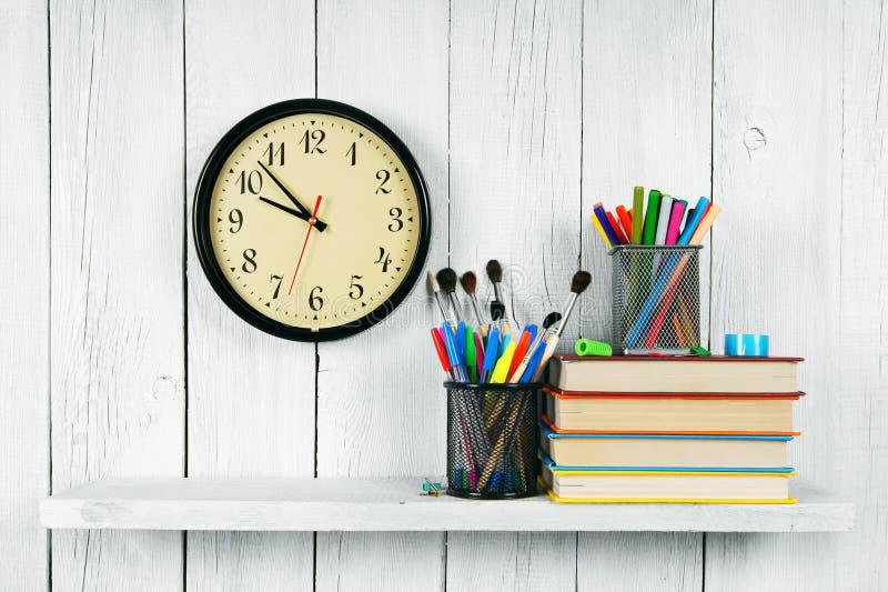 Uhren, Bücher und Schulwerkzeuge auf hölzernem Regal stockfotografie