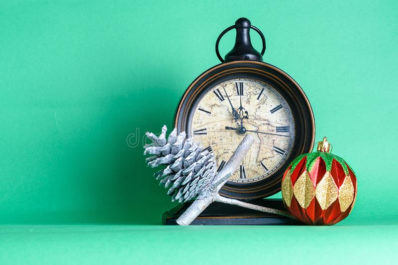 Uhrmitternacht, -flitter und -kegel des neuen Jahres auf Kieferntannenbaumast Gr?ner Hintergrund Weihnachtsmann auf einem Schlitt stockfoto