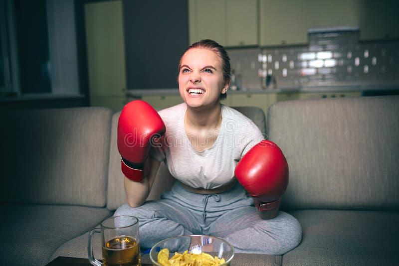 Uhrverpacken der jungen Frau im Fernsehen nachts Emotionales verärgertes Modell schauen oben vorwärts Ver?rgertes Gesicht Hände i lizenzfreies stockbild