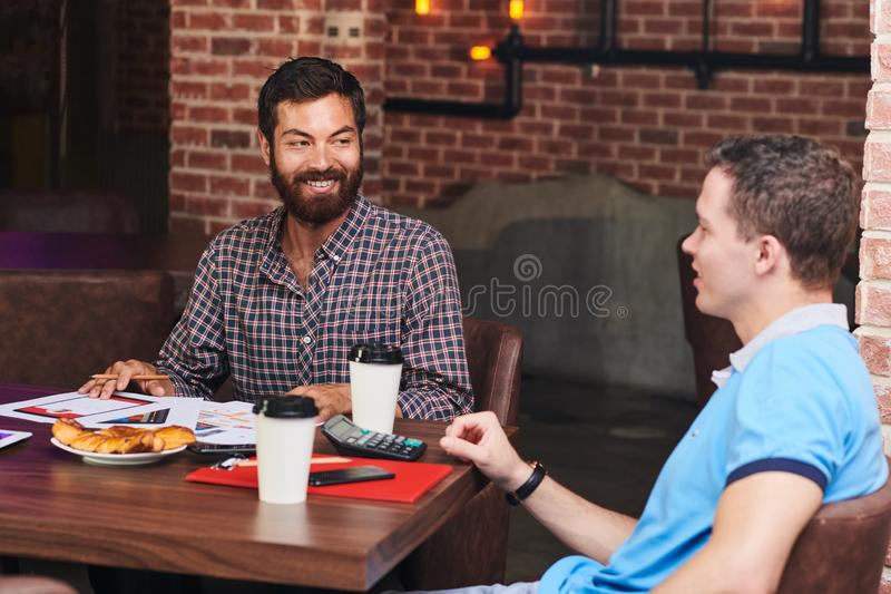 UI designer discussing project with financial manager. Cheerful bearded UI designer discussing project of new mobile application with financial manager at stock photography