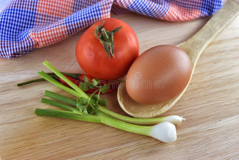 Ui, ei, Spaanse peper en tomaat op houten achtergrond stock foto's