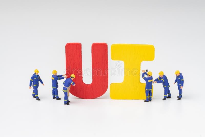 UI gebruikersinterfaceontwikkeling en ontwerpconcept, het miniatuurteam die van mensenarbeiders het kleurrijke woord UI met wit b stock fotografie