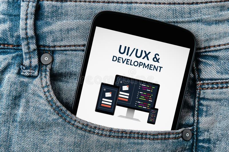 UI/UX设计和发展概念在智能手机屏幕上在牛仔裤装在口袋里 图库摄影