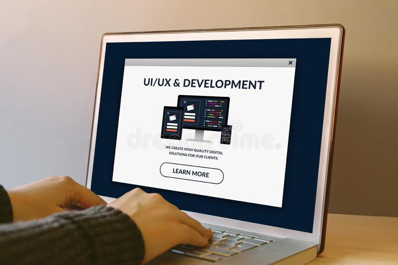 UI/UX design and development concept on laptop screen on wooden table. UI/UX design and development concept on laptop computer screen on wooden table. Hands royalty free stock photo
