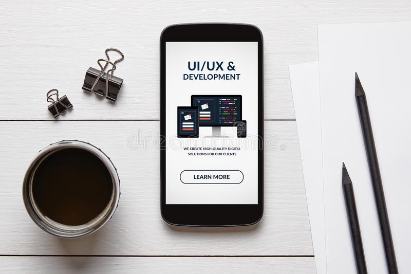 UI/UX design and development concept on smart phone screen with office objects. On white wooden table. All screen content is designed by me. Flat lay royalty free stock images