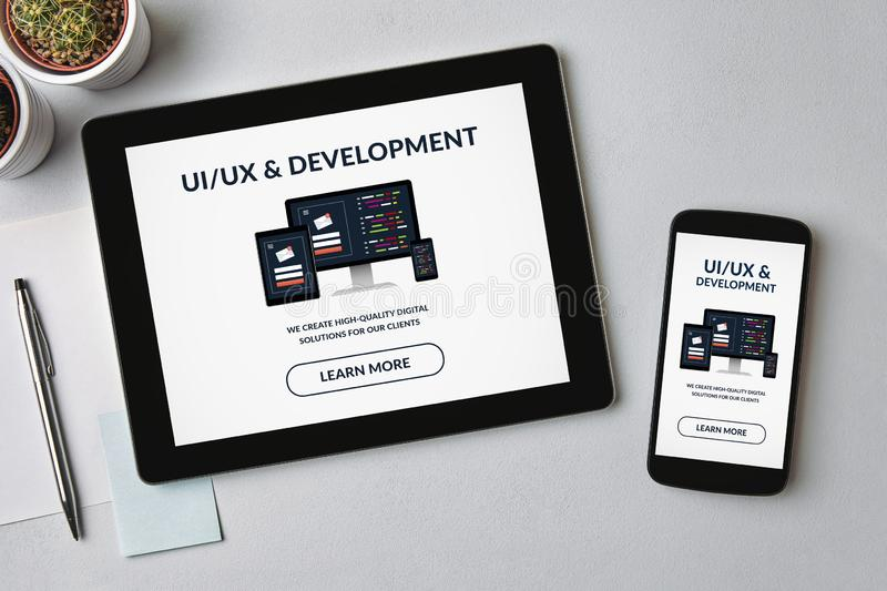 UI/UX design and development concept on tablet and smartphone screen. Over gray table. All screen content is designed by me. Flat lay royalty free stock photography