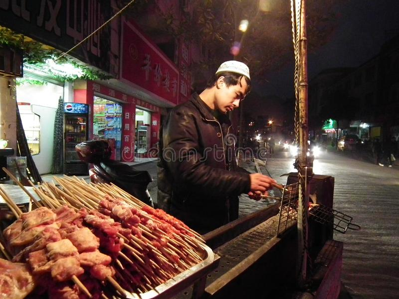 Uighur man selling skewers in night market, Xinjiang, China stock afbeeldingen