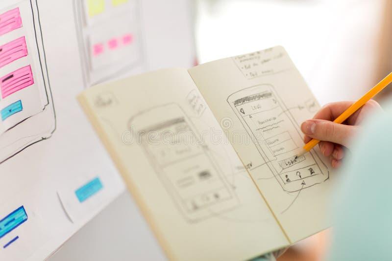 Uiontwerper met gebruikersinterfaceschets in notitieboekje royalty-vrije stock afbeelding