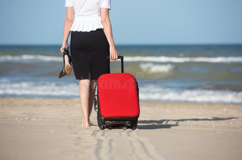"""Uit bureau†""""vakantie op zee De vrouw sleept de koffer over het zand aan de kust stock afbeelding"""