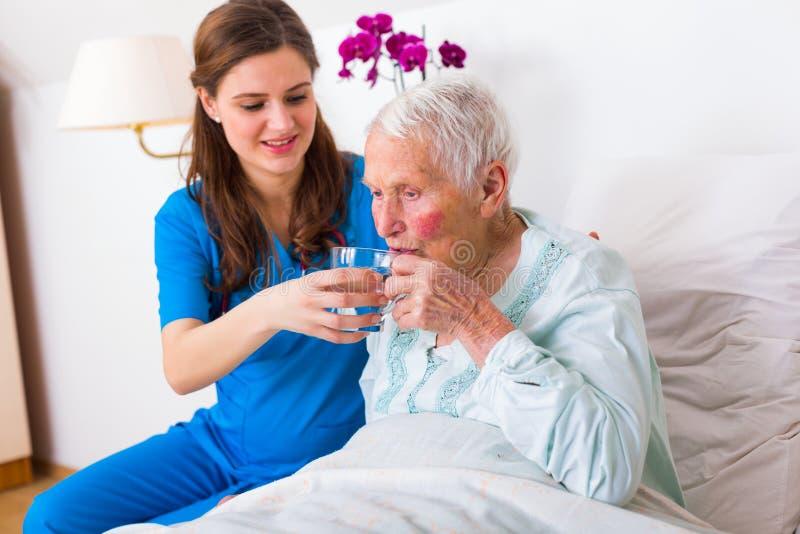 Uit het helpen van bejaarde patiënt stock foto