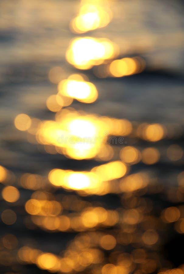 De achtergrond van Bokeh van overzees water met zonbezinningen royalty-vrije stock afbeelding