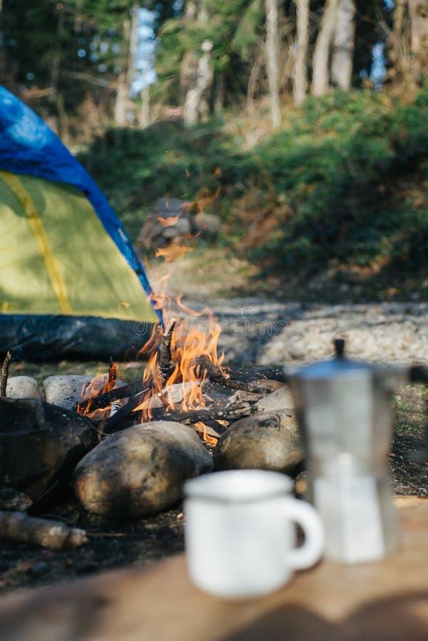 Uit nadrukbeeld van mok en koffiezetapparaat dichtbij vuur in bergen Selectieve nadruk op een kampvuur met vage achtergrond royalty-vrije stock fotografie