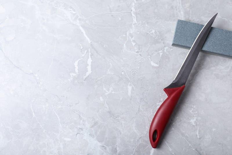 Uitbenend mes, die steen en ruimte voor tekst op grijze achtergrond scherpen royalty-vrije stock afbeelding